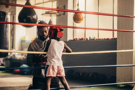Rear view of a boxing kids talking to his coach standing inside the boxing ring. Kid wearing boxing gloves and head guard standing inside a boxing ring.