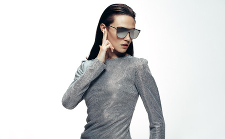 Portrait of attractive woman in sliver outfit and mirrored glasses looking away with fingers over her ear. Woman in robotic style against white background.