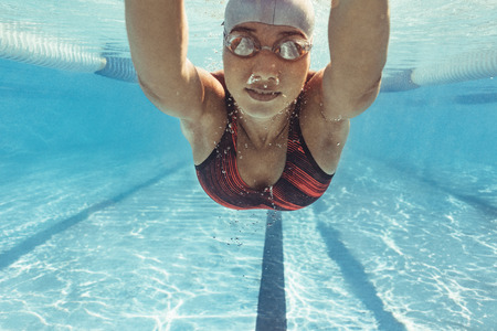 Underwater shot of female swimmer swimming inside pool. Fit young female swimmer training in the pool.
