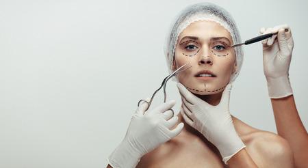 Horizontale Aufnahme der Frau unter einer Facelifting-Operation. Weibliches Gesicht mit gepunkteter Linie gezeichnet und Kosmetikerin, die chirurgische Instrumente auf grauem Hintergrund hält.