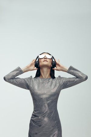 Vertical shot of caucasian woman wearing headphones and looking up over grey background. Stylish female model in robotic look.