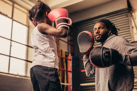 Boxing coach wearing punching pads in hands training a little girl. Boxing girl training with her coach inside a boxing ring. Stock Photo