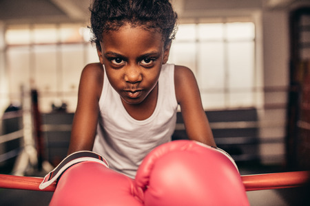 Kid wearing boxing gloves standing inside a boxing ring. Boxer kid resting her hands on boxing ring with determination and focus in her eyes.