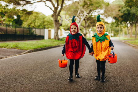 Two little girls in halloween costume trick or treating on the road. Two identical twin sisters in halloween costume walking outdoors with halloween bucket. Stock Photo