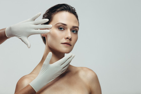 Beautician hands with gloves touching beautiful woman face before plastic surgery. Female standing against grey background with a cosmetologist touching her face.
