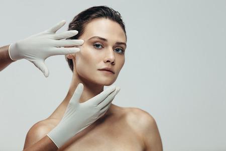 Kosmetikerhände mit Handschuhen, die schönes Frauengesicht vor plastischer Chirurgie berühren. Frau, die gegen grauen Hintergrund mit einer Kosmetikerin steht, die ihr Gesicht berührt.