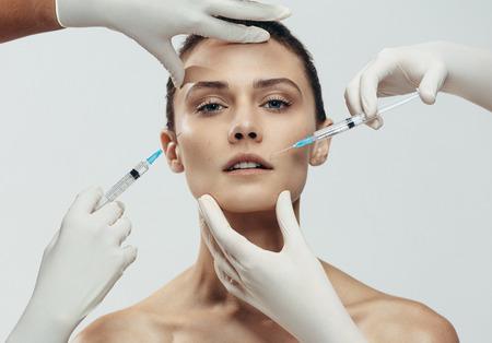 La giovane donna riceve l'iniezione nelle labbra e nella guancia dai cosmetologi. Due mani di estetista in guanti che danno siero anti invecchiamento sparato sul viso femminile su sfondo grigio.