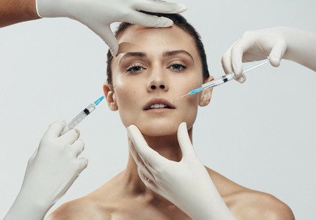 Young woman gets injection in her lips and cheek by cosmetologists. Two beautician hands in gloves giving anti aging serum shot on female face against grey background.