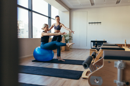 Female pilates instructor training a woman in pilates workout. Woman doing pilates workout sitting on a fitness ball in a gym.