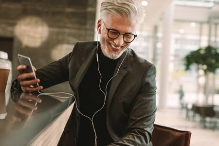 Smiling mature male in business suit sitting at cafe in earphones and holding a mobile phone. Business man making phone call using earphones in coffee shop. Stock Photo