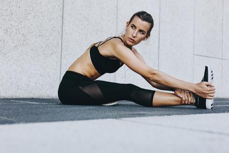 Fitness vrouw haar benen strekken voor training buiten zitten. Vrouwelijke loper die rekoefeningen doet die naar muziek luisteren.