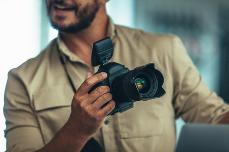 Portrait of a photographer holding a DSLR camera. Photographer holding a digital camera and talking.