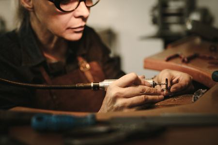 Senior female jewelry maker polishing a product at her workbench. Jewelry designer polishing a bracelet at workshop.