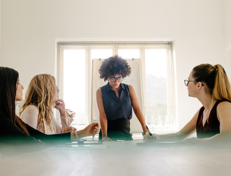 Young african businesswoman sharing her ideas to female colleagues sitting around conference table in modern office. Group of women having a meeting in boardroom.