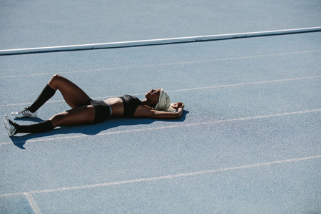 Woman athlete lying on the running track relaxing after training. Female sprinter resting after workout lying on track on a sunny day.