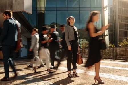 Femme d'affaires tenant son sac à main immobile dans une rue animée avec des passants devant elle à l'aide de téléphones portables. Femme debout au milieu d'un bureau occupé va foule accrochée à leurs téléphones portables.