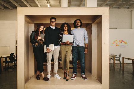 Creative business colleagues standing together holding laptops and digital tablet in office. Entrepreneurs standing inside a wooden cubicle enclosure in office.