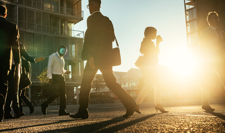 Men and woman commuting to office early in the morning carrying office bags with sun flare in the background. Businesswoman walking on a busy city street to office drinking coffee.