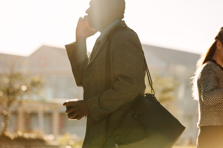 Businessman commuting to office talking over mobile phone with a coffee cup in hand with sun flare in the background. Busy man walking to office carrying his office bag holding and a coffee cup in one hand and talking over mobile phone with the other.