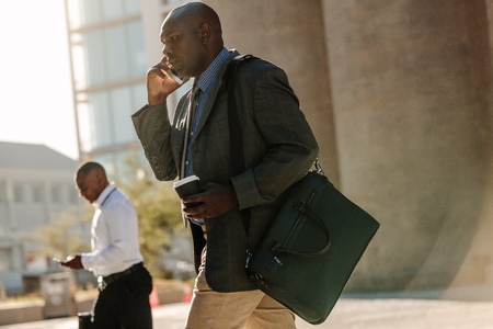Men using mobile phone while commuting to office. Businessmen leading a busy life using mobile phones and drinking coffee while walking on street to office.