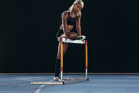 Female athlete standing on a running track resting one leg on a hurdle. Stock Photo