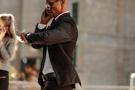 Man looking at his wrist watch and talking over mobile phone while commuting to office in the morning. Businessman checking time while walking to office.