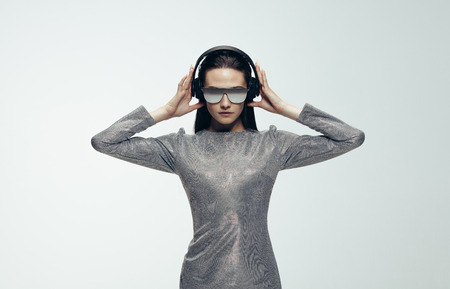 Portrait of woman wearing headphones over grey background. Stylish female model in silver dress, sunglasses and headphone. Stok Fotoğraf