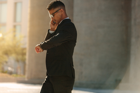 Man in formal clothes looking at his wrist watch and talking over mobile phone while walking on street.