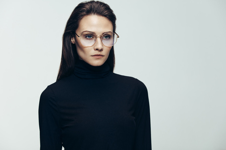 Stunning young woman in black clothes wearing glasses. Female model in studio looking away with blank expression on grey background. Stock Photo