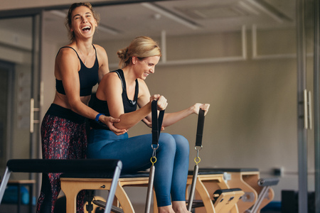 Laughing female trainer helping a woman in pulling stretch bands sitting on pilates training machine. Smiling woman at the gym doing pilates training with her trainer. Фото со стока