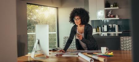 Vrouw interieurontwerper met kleurstaal in de hand werken op de computer in het kantoor aan huis. Jonge afrikaanse vrouw die aan tafel staat en op zoek is naar een kleur terwijl ze een ontwerp maakt op de computer. Stockfoto