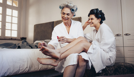 Mother applying nail paint to the feet of her daughter at home. Mother and daughter in bathrobe with rollers pinned on head.