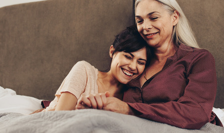 Happy daughter and mother lying on bed holding hands. Smiling woman with her head on shoulder of her mother sitting on bed. 스톡 콘텐츠 - 111942482
