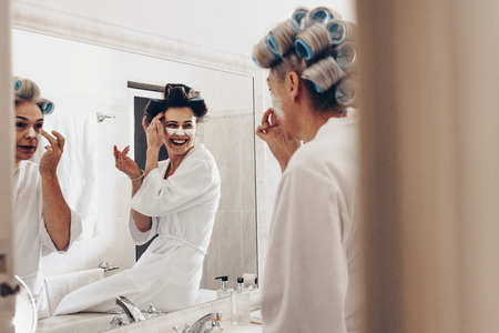 Two women in bathrobes applying cream on face standing in front of mirror. Women with curling rollers pinned on hair grooming at home.