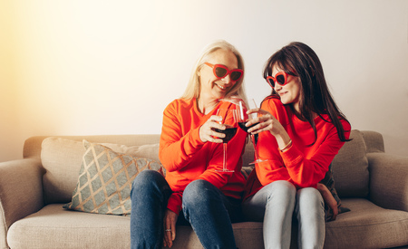 Two women wearing similar outfit toasting glasses of wine sitting at home. Women in fancy eyewear sitting together on a couch drinking wine. 스톡 콘텐츠