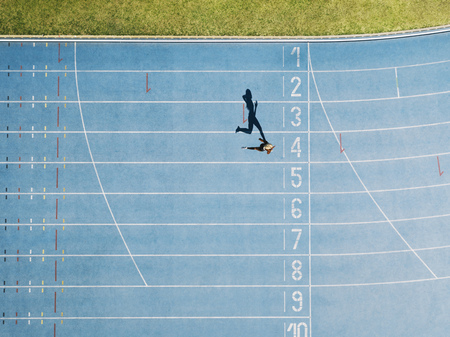 Female sprinter running on athletic track nearing the finish line. Top view of a sprinter running on race track in a stadium.