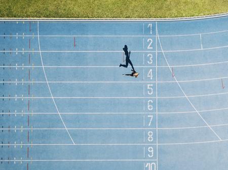 Velocista femenina corriendo en pista de atletismo acercándose a la línea de meta. Vista superior de un velocista corriendo en la pista de carreras en un estadio. Foto de archivo