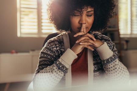 Afrikanische Frau, die an ihrem Schreibtisch sitzt und mit geschlossenen Augen denkt. Gestresste Frau, die eine Pause einlegt, um mit Achtsamkeit eine Lösung zu finden.