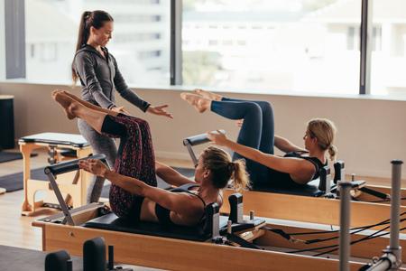 Donne che fanno esercizi di pilates sdraiate su macchine per l'allenamento pilates mentre il loro allenatore le guida. Due donne fitness vengono addestrate da un istruttore di pilates. Archivio Fotografico