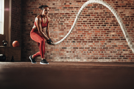 Woman using training rope for exercise at gym. Athlete working out with battle rope at cross training gym. Stock Photo