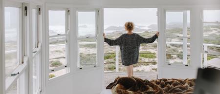 Donna in piedi vicino alla porta del balcone di una casa sulla spiaggia che gode della vista sul mare. Donna che indossa un grande maglione guardando il mare.
