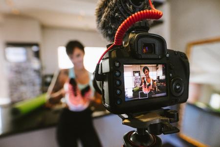 Vrouwelijke vlogger die sportschoenen in handen houdt en gelukkig in de camera kijkt tijdens het opnemen van video voor blog. Focus op de camera met social media influencer die een sportschoen beoordeelt en op de markt brengt. Stockfoto