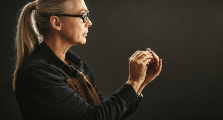 Senior woman jeweler wearing eyeglasses and apron looking at the quality of ring against gray background. Goldsmith examining the ring for flaws. Standard-Bild - 111956930