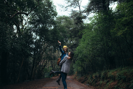 Man carrying her girlfriend raising hand and smiling. Couple enjoying themselves at forest on rainy day. Banque d'images