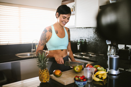 Smiling woman cutting fruits in kitchen and recording it on video. Young woman in kitchen recording content for videoblog. Stock Photo