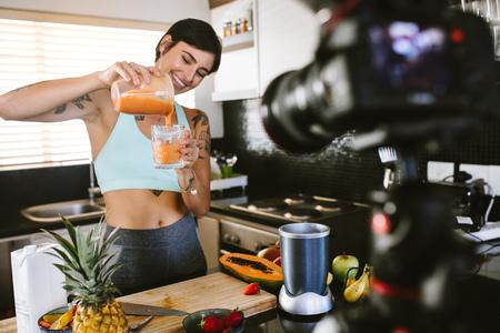 Femme versant un smoothie frais dans un verre d'un presse-agrumes. Blogueur culinaire enregistrant un vlog à la caméra sur un smoothie frais et sain.