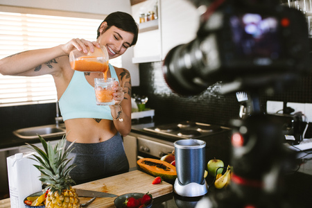 Frau, die aus einem Entsafter frischen Smoothie in ein Glas gießt. Food-Blogger, der vor der Kamera einen Vlog über frischen und gesunden Smoothie aufzeichnet