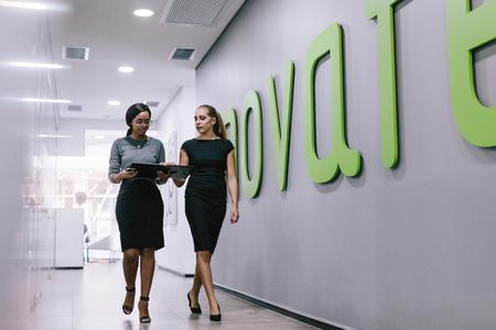 Deux femmes d'affaires marchant dans le couloir du bureau et regardant un dossier. Des professionnels discutent du travail dans un couloir de bureau moderne. Banque d'images