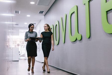 Two business women walking through office corridor and looking at a file. Business professionals discussing work in modern office hallway. Standard-Bild