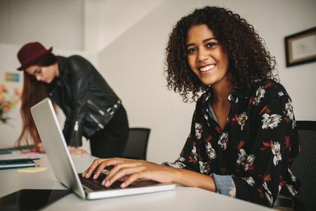 Geschäftsfrau, die an Laptop-Computer im Büro arbeitet, das im Konferenzraum sitzt. Geschäftskollegen, die im Büro zusammenarbeiten.